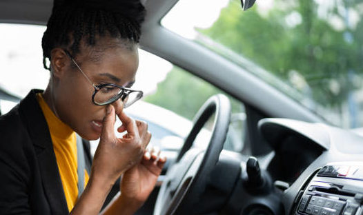 Woman sitting in smelly car